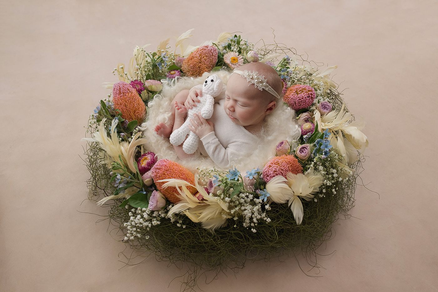 baby girl lying in a floral nest in a photography studio in Perth, Western Australia