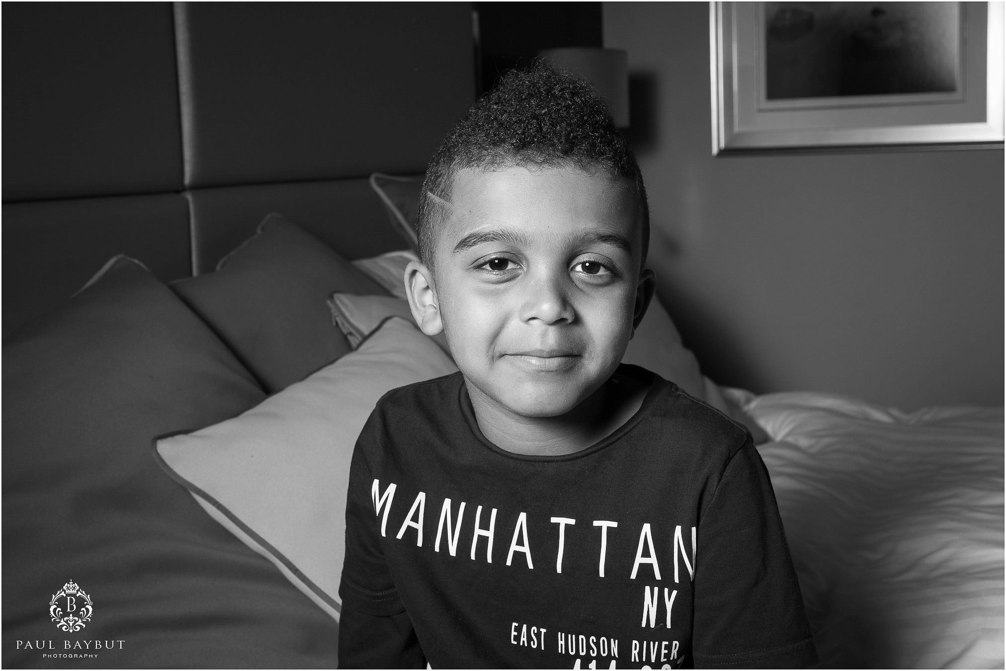 Portrait of little black boys face whilst sitting on a bed