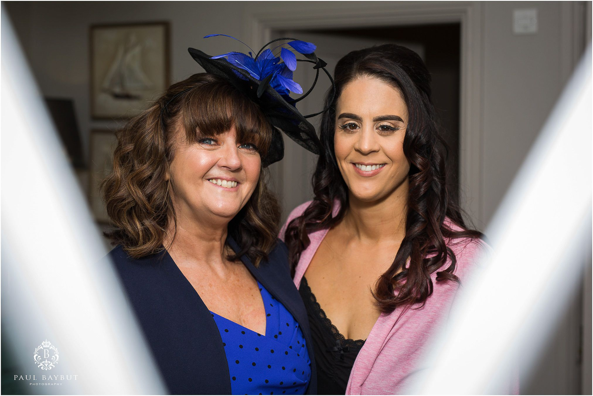 Mother and daughter smile together in the mirror at a wedding at Abbey House in Cumbria