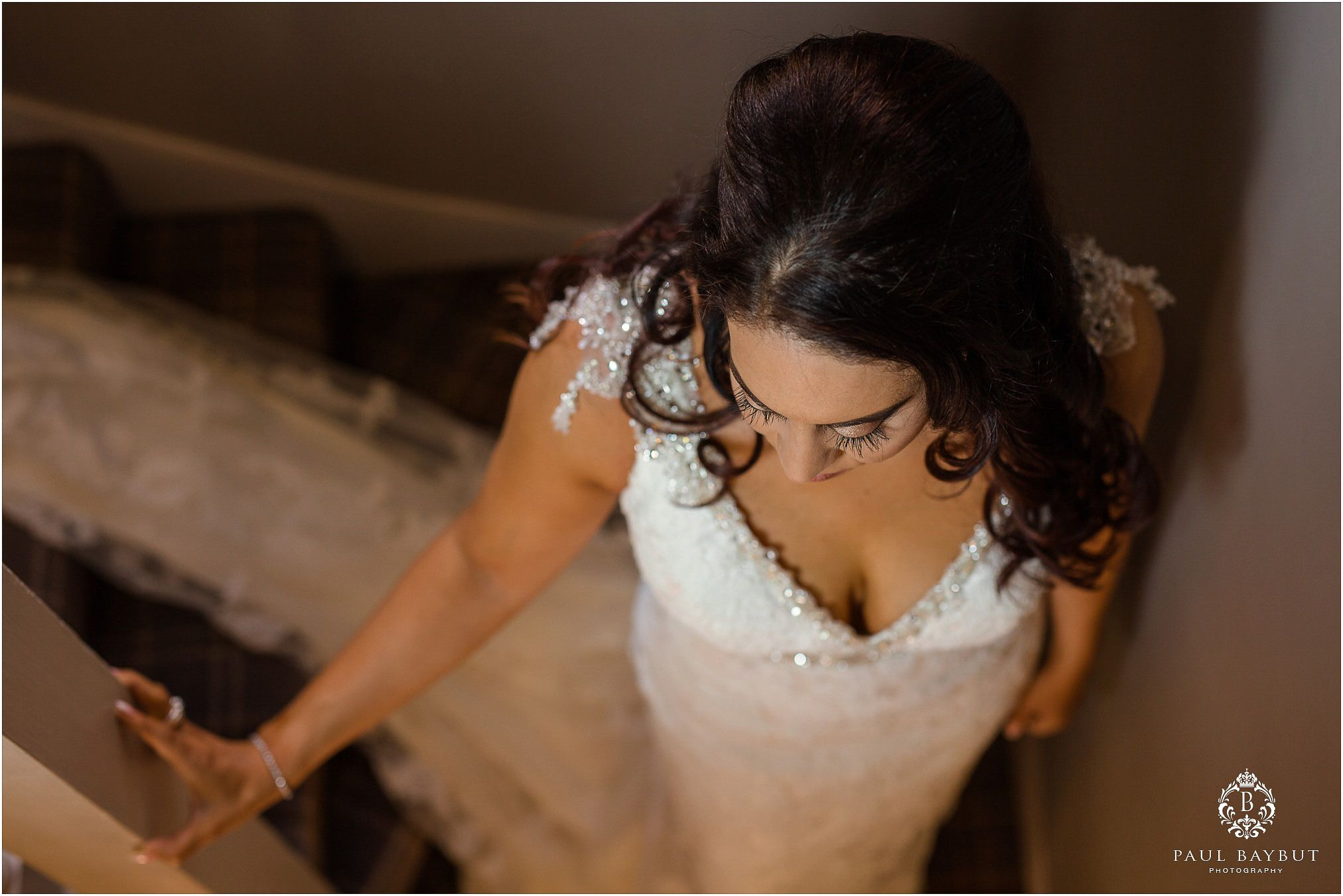 Bride in white dress stands midway on the stairs at Abbey House in Cumbria