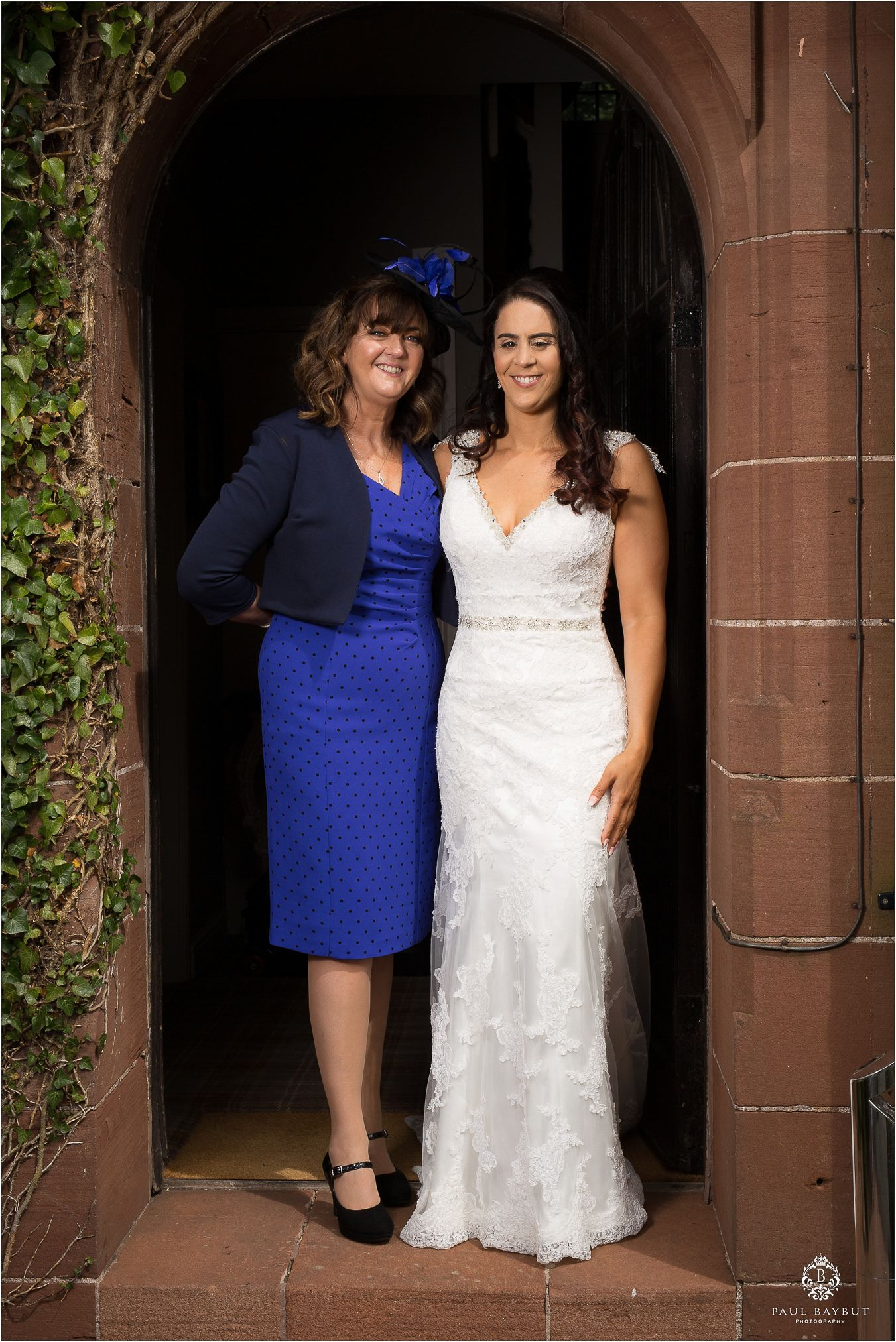 Mother in blue dress and daughter in white wedding dress stand in a doorway for a photograph