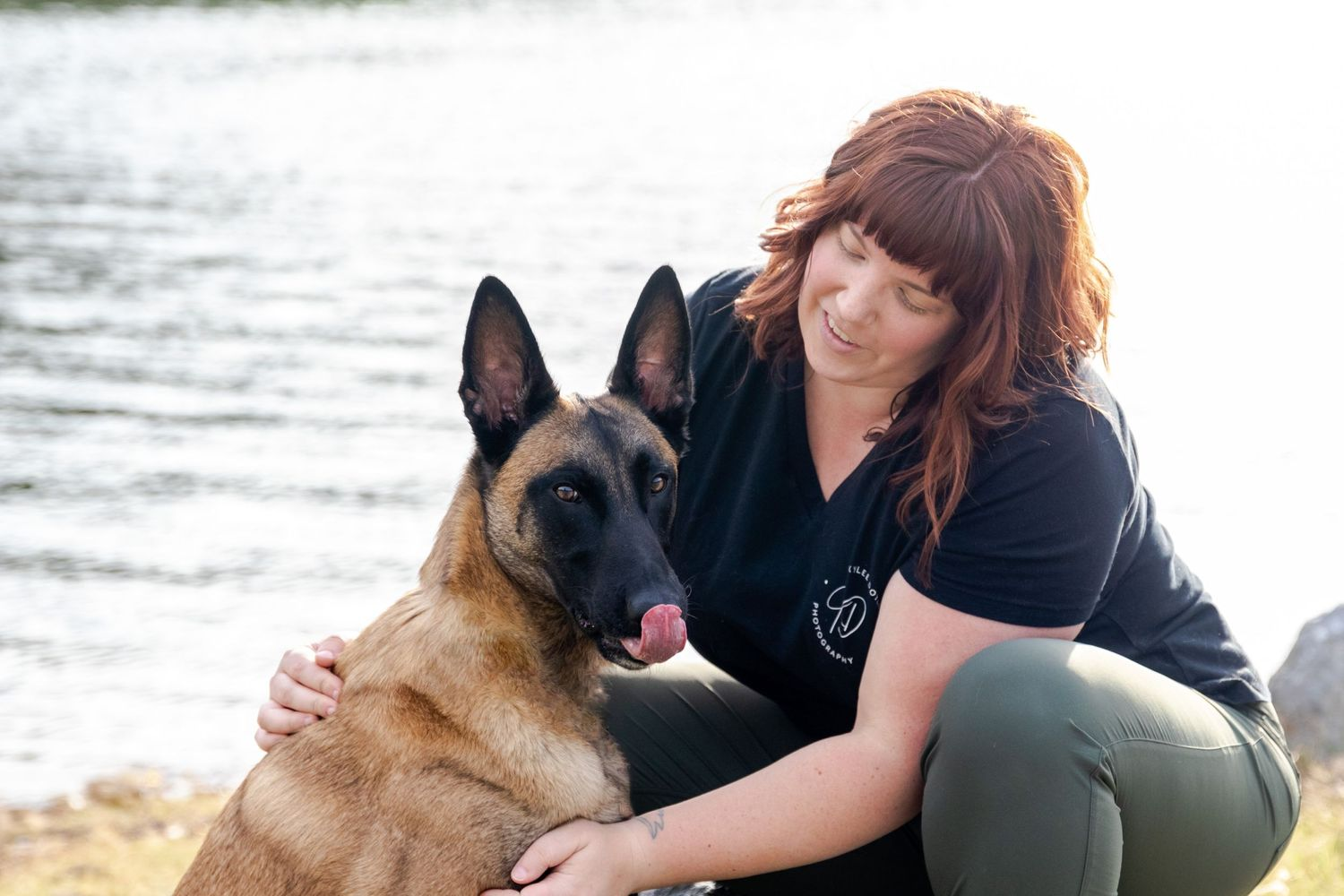 Owner of Kylee Doyle Photography, interacting with a belgian malinois, who is looking at the camera and licking his nose