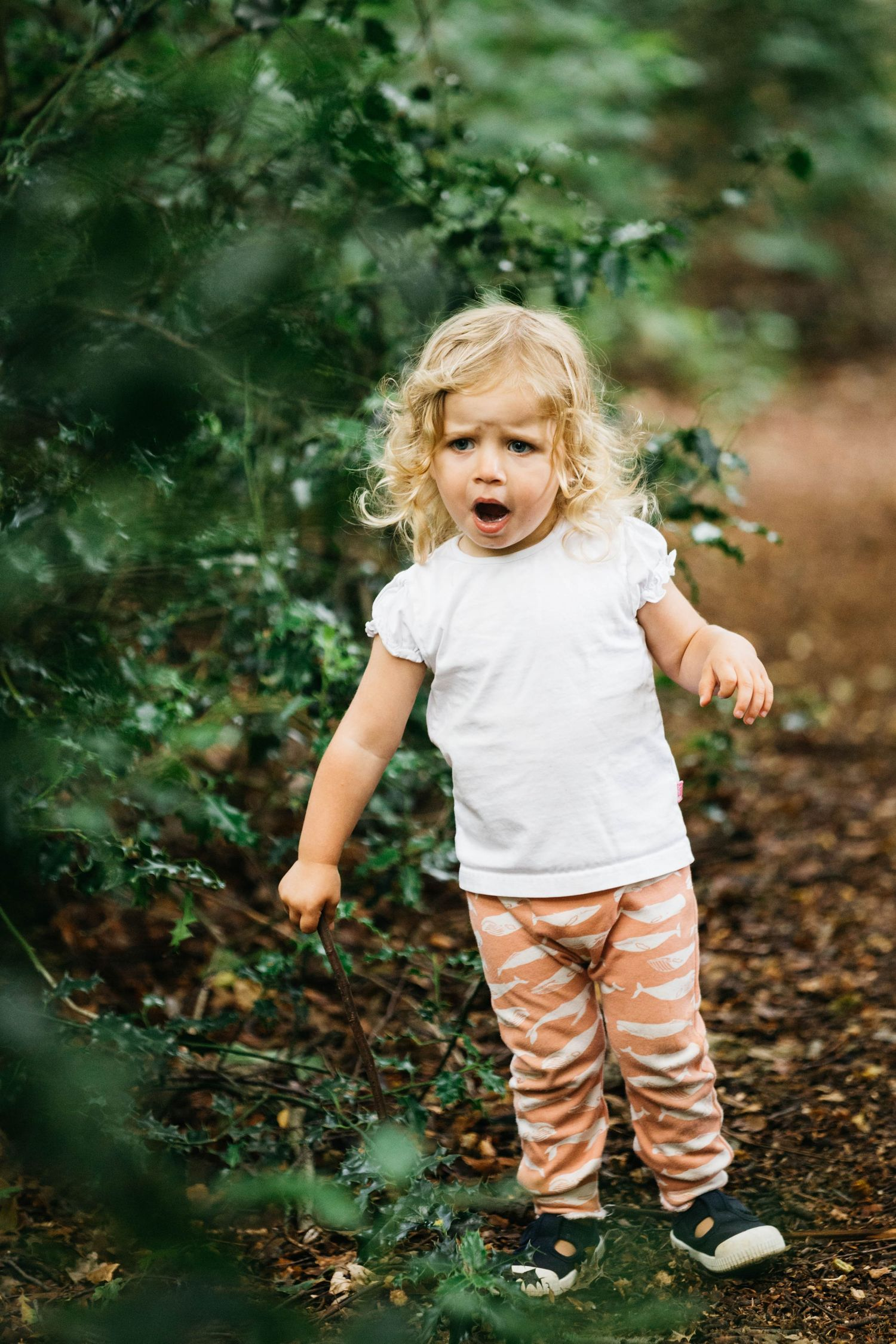 toddler girl with blonde hair pulling faces