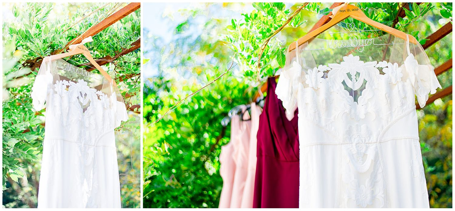 wedding dress and red and blush bridesmaids dresses hanging side by side for a fall wedding in California