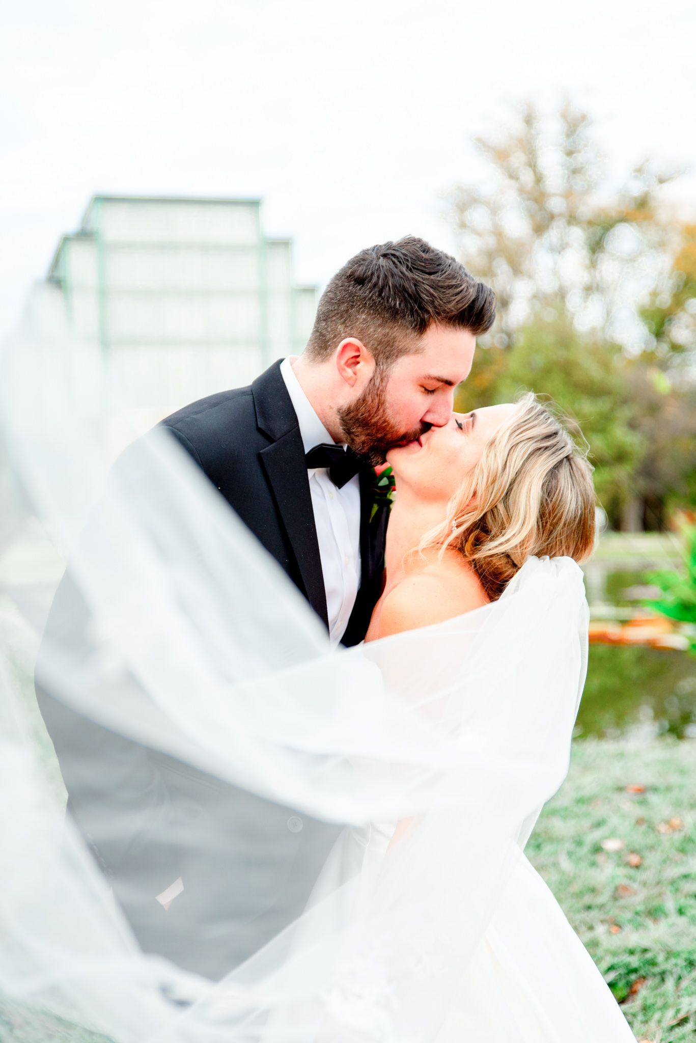 bride and groom kissing with veil in pictures on fall wedding day