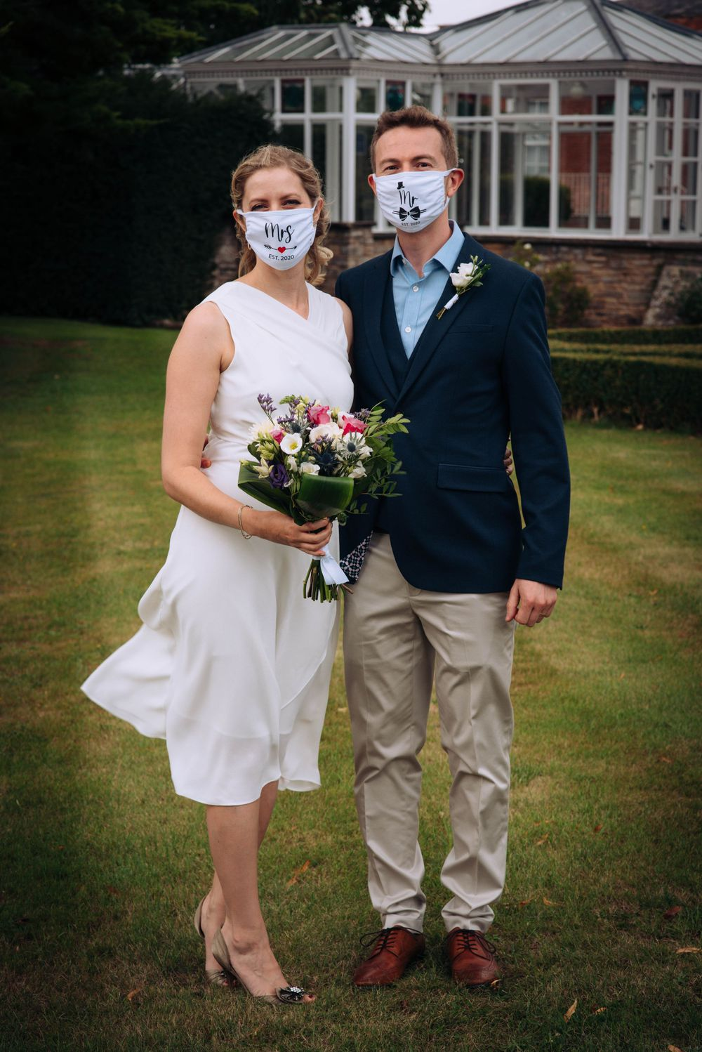 Pukrup Hall wedding by Zara Davis Photography, Gloucestershire bride and groom wearing masks outside