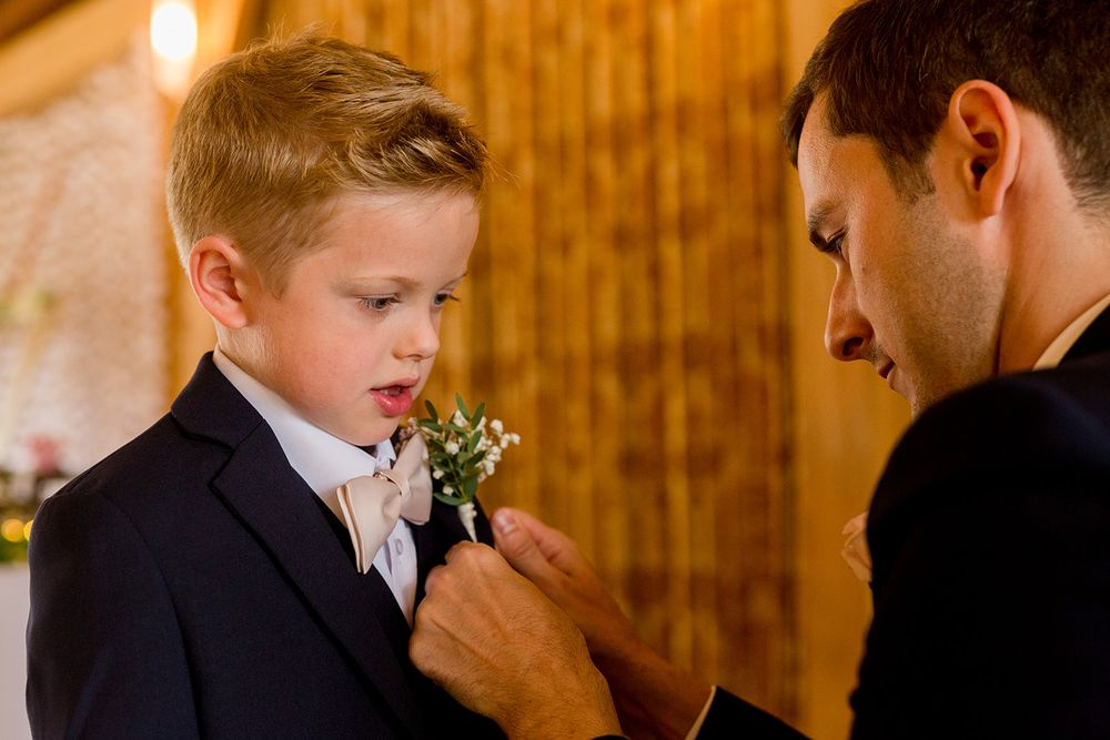 groom helping ring bearer with botton hole