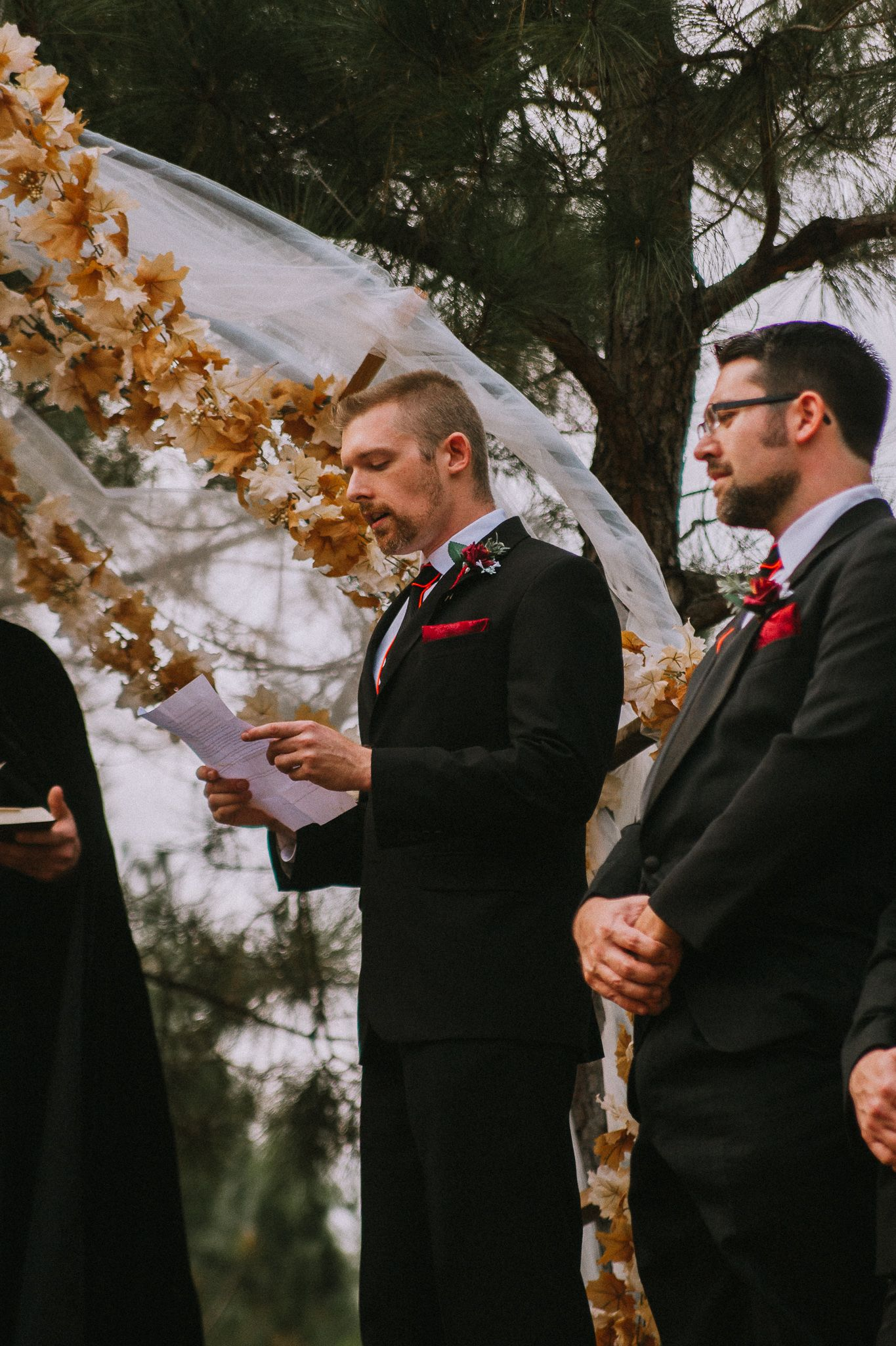 groom saying vows in front of friends and family