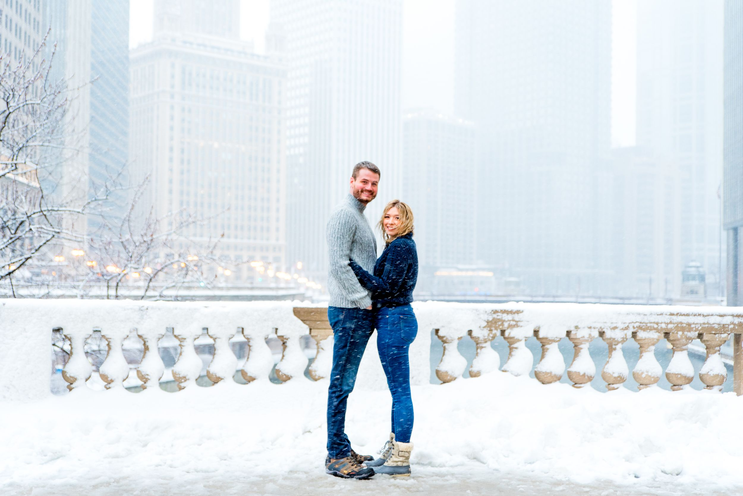 couple hugging in the snow at Wrigley Building overlooking the Chicago River for snowy winter engagement pictures