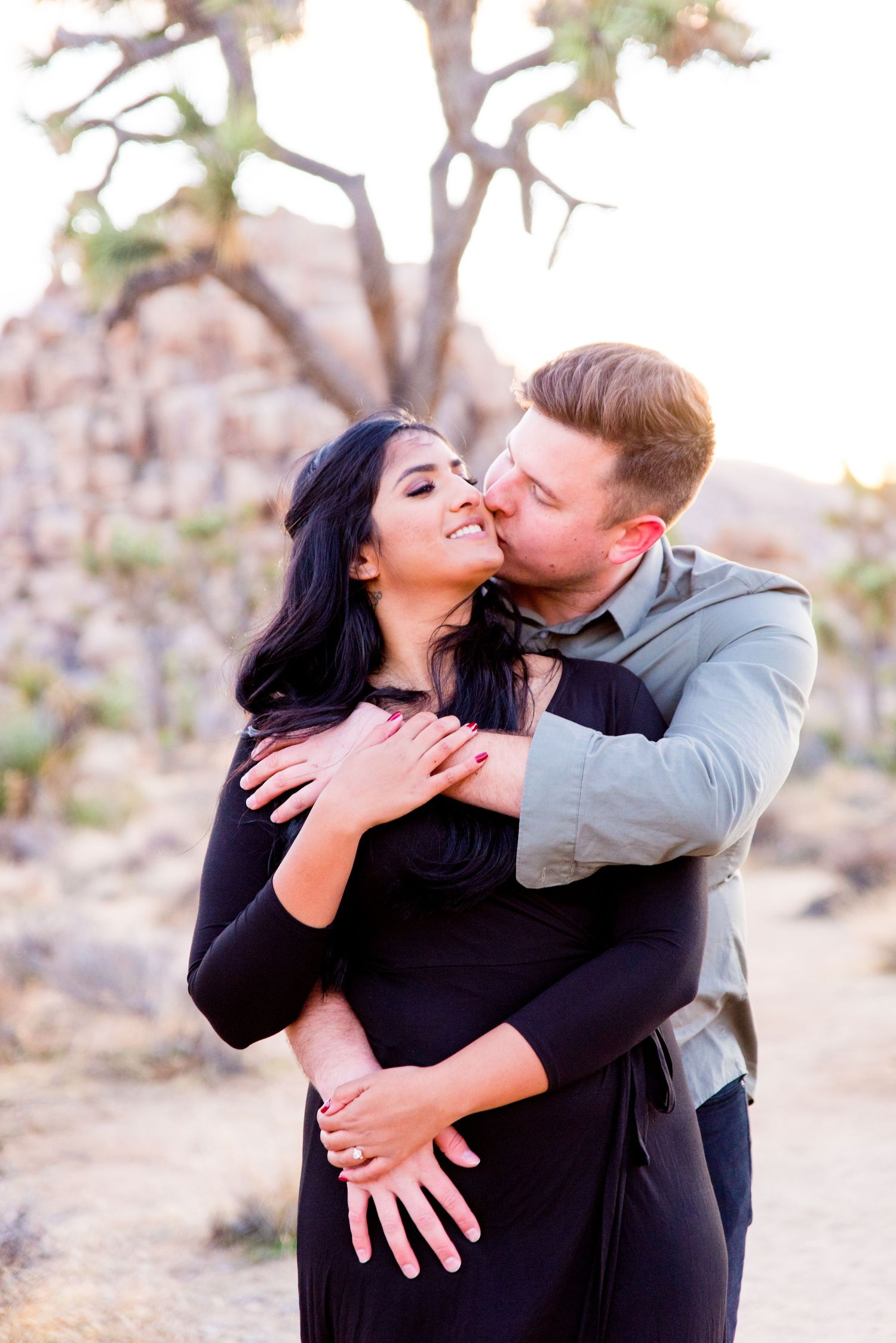 man in gray shirt kissing his fiancee in a black dress while hugging her from behind at Joshua Tree National Park