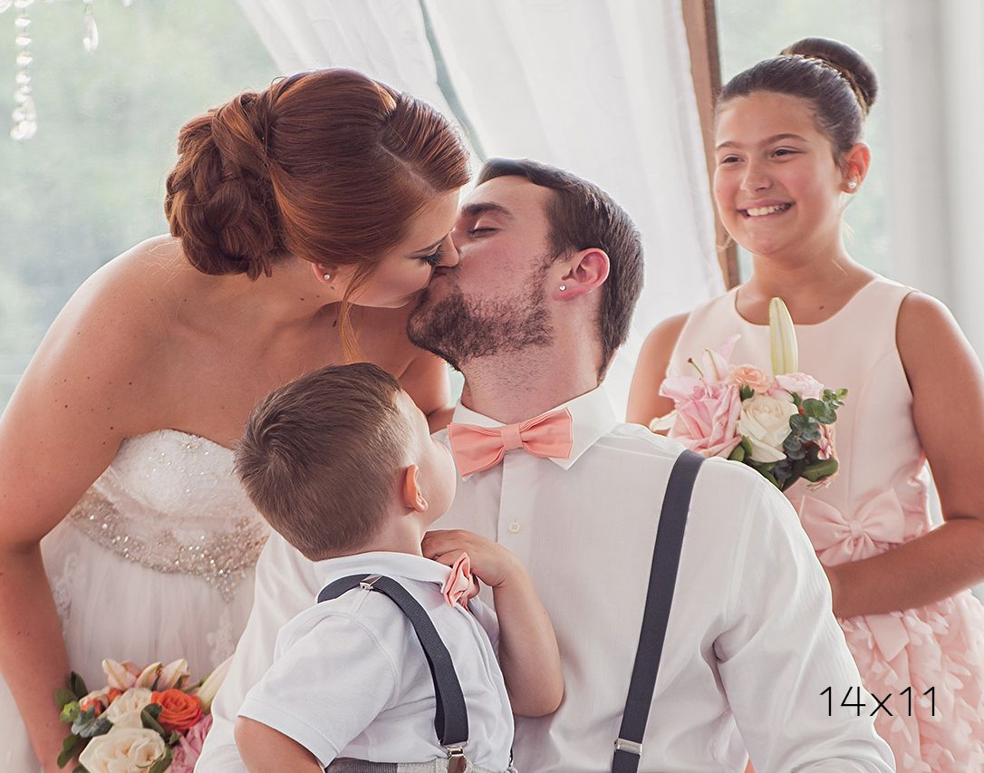 14x11 image of bride and groom kissing while children look on