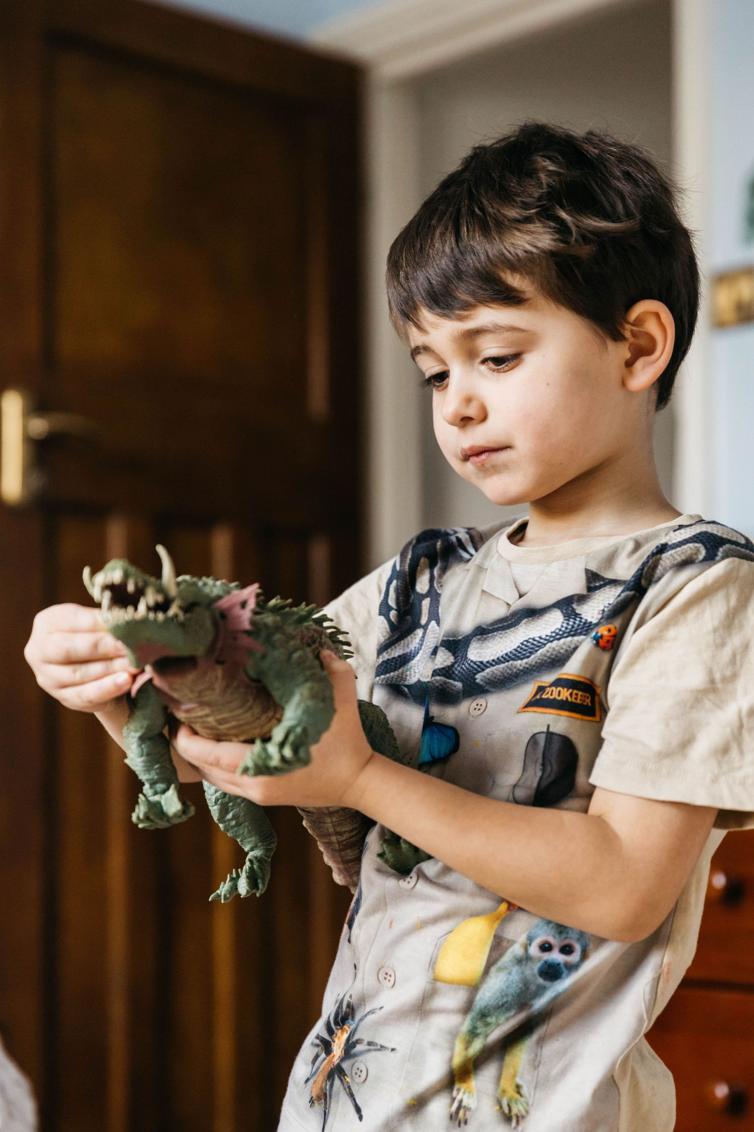 boy looking seriously at his toy dinosaur
