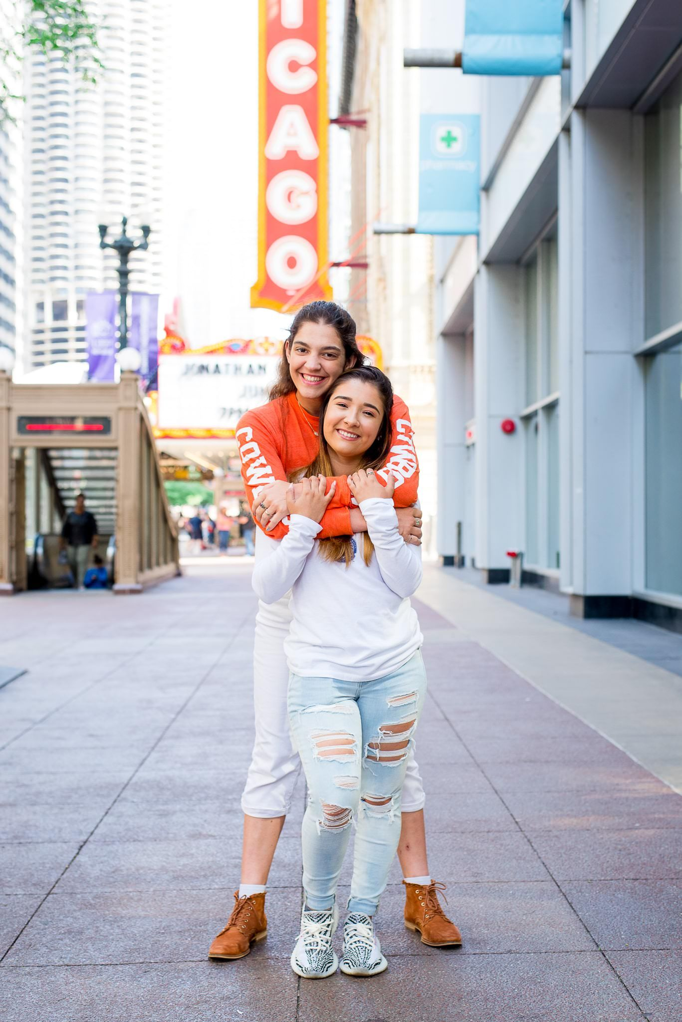two senior girls in front of the Chicago Theater sign for Chicago senior pictures hugging each other