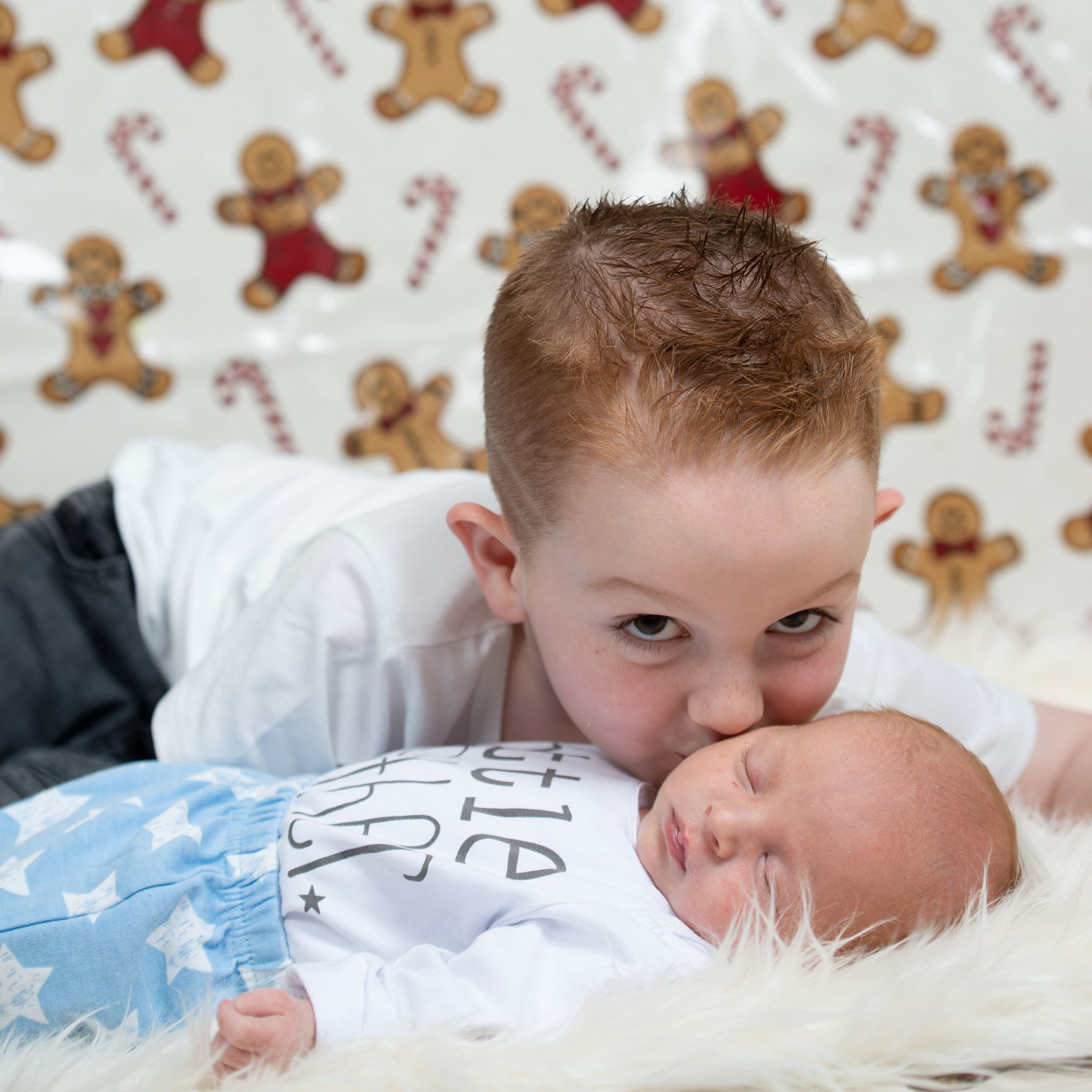 young ginger haired boy kisses his newborn brother ballymoney newborn photographer