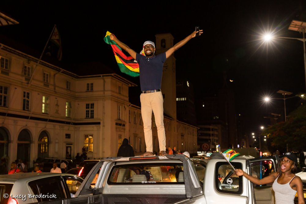 Victory.  21 November 2017. A Zimbabwean Man celebrates his freedom after Mugabe's resignation outside his old office