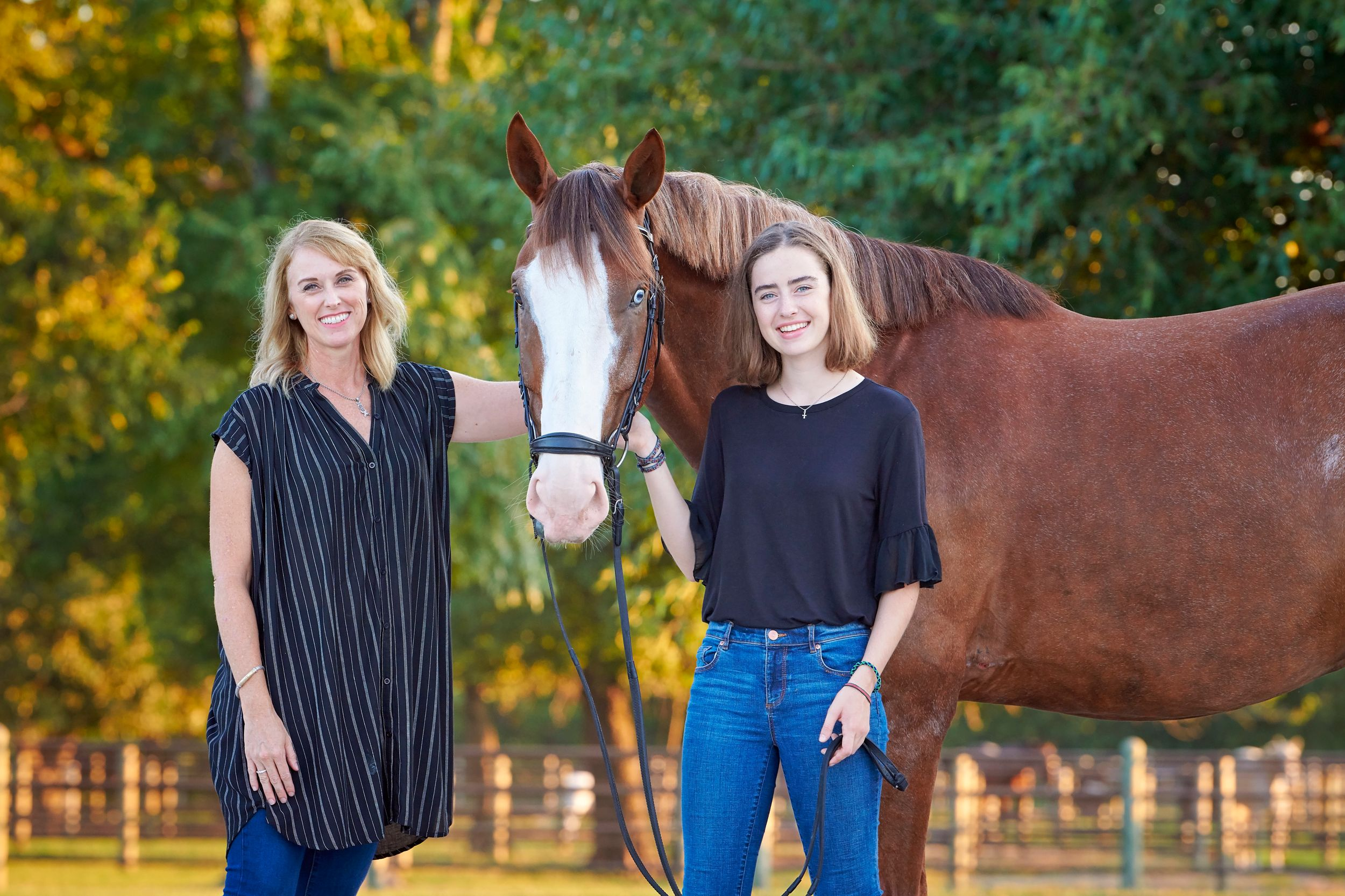 Mother and daughter posing with Warmblood horse