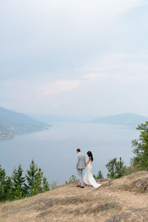 bride and groom walking with okanagn lake view