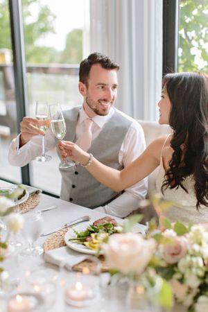 bride and groom clinking wine glasses