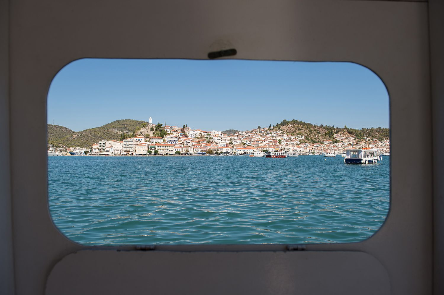 Poros island through small boat window