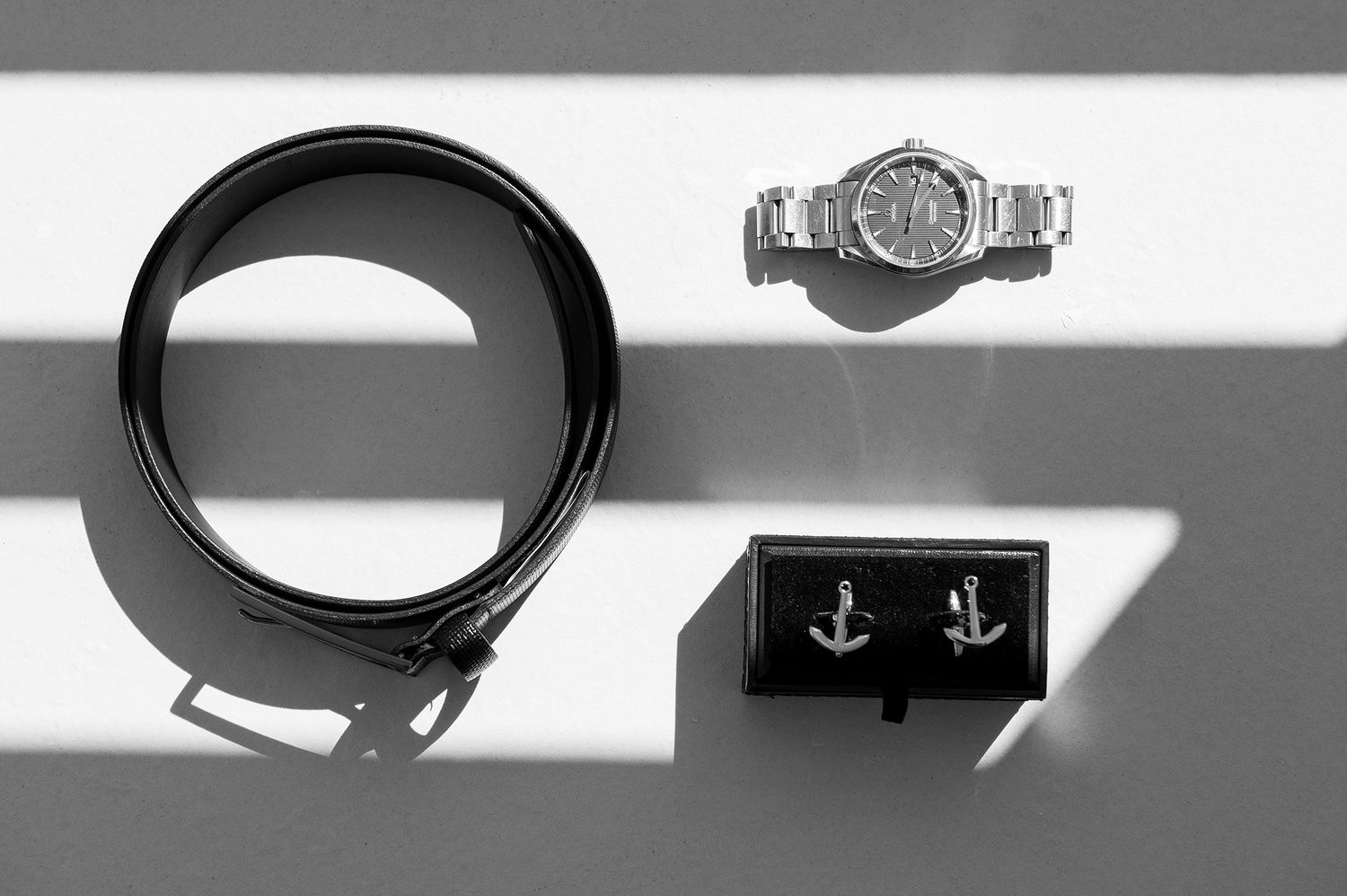 groom's watch belt and cufflinks under greek sunlight and shadows