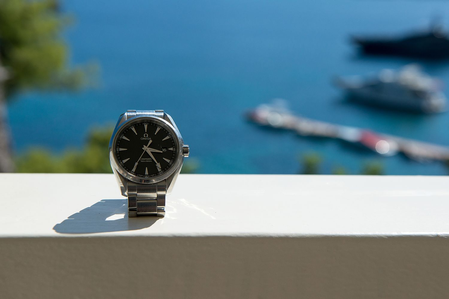 groom's omega watch in front of the blue sea of poros