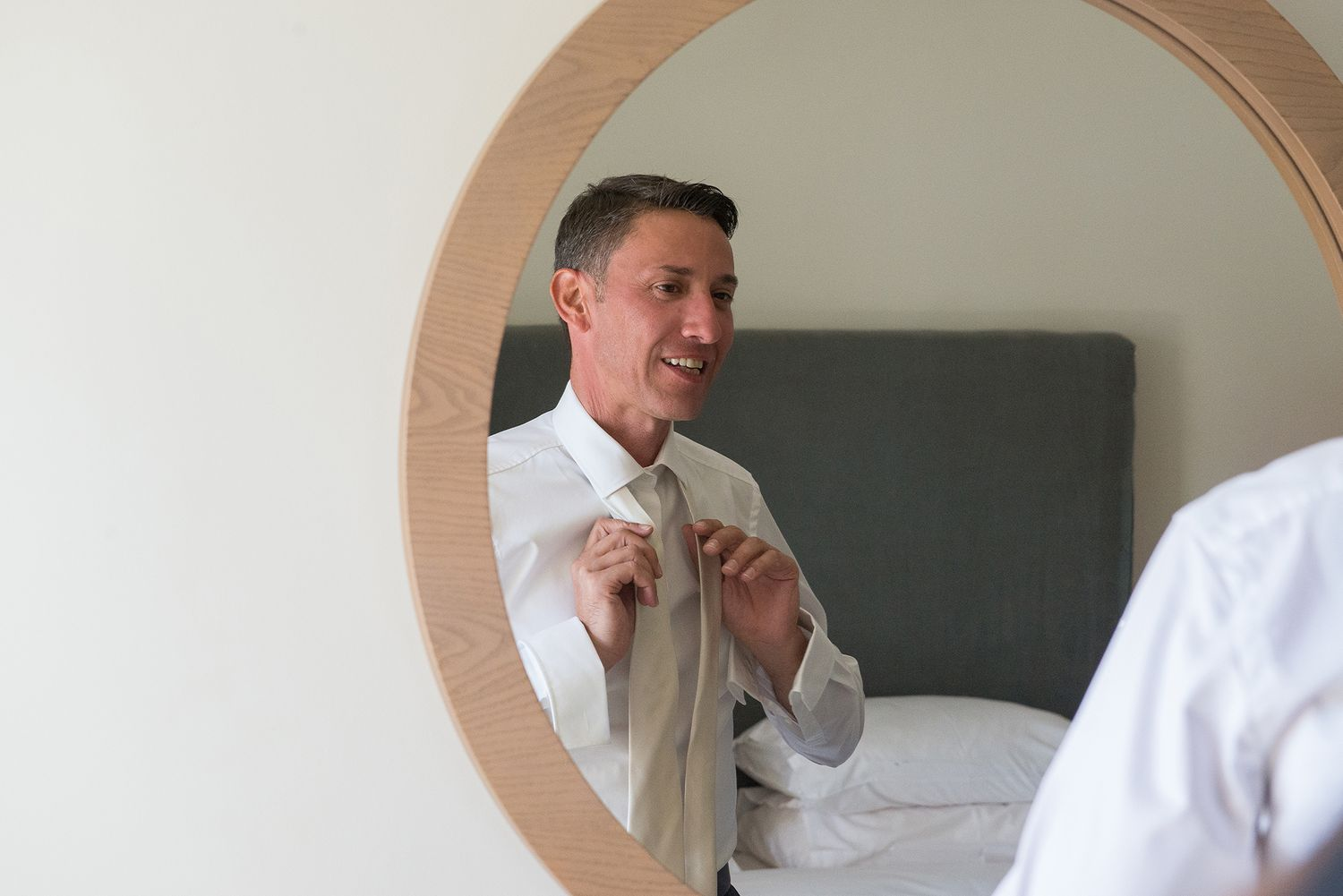 groom fixes his tie in front of the mirror at his preparation before the wedding