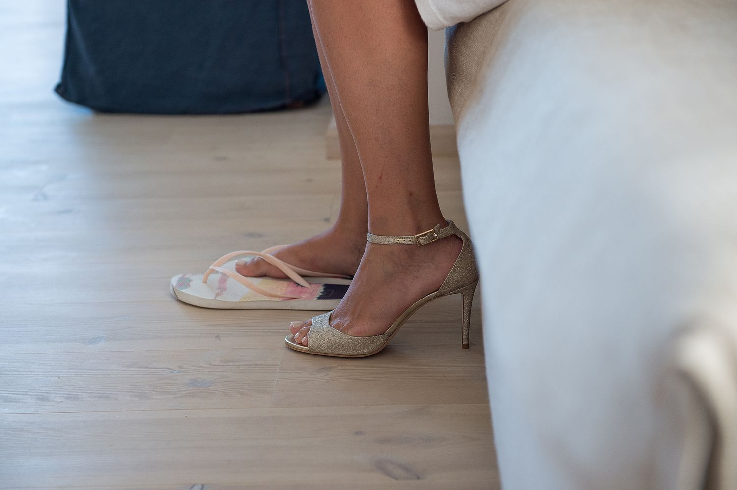 bride's foot while putting on the wedding shoes