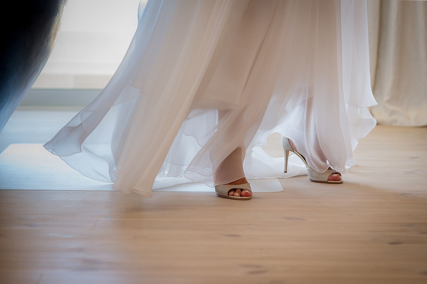 bride's feet wearing jimmy choo wedding heels