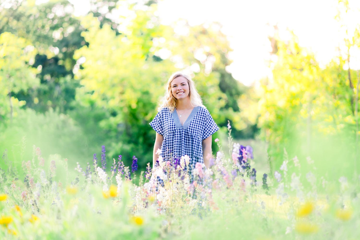 blonde woman standing in field of yellow and purple flowers at The Marmalade Lily in Ohio