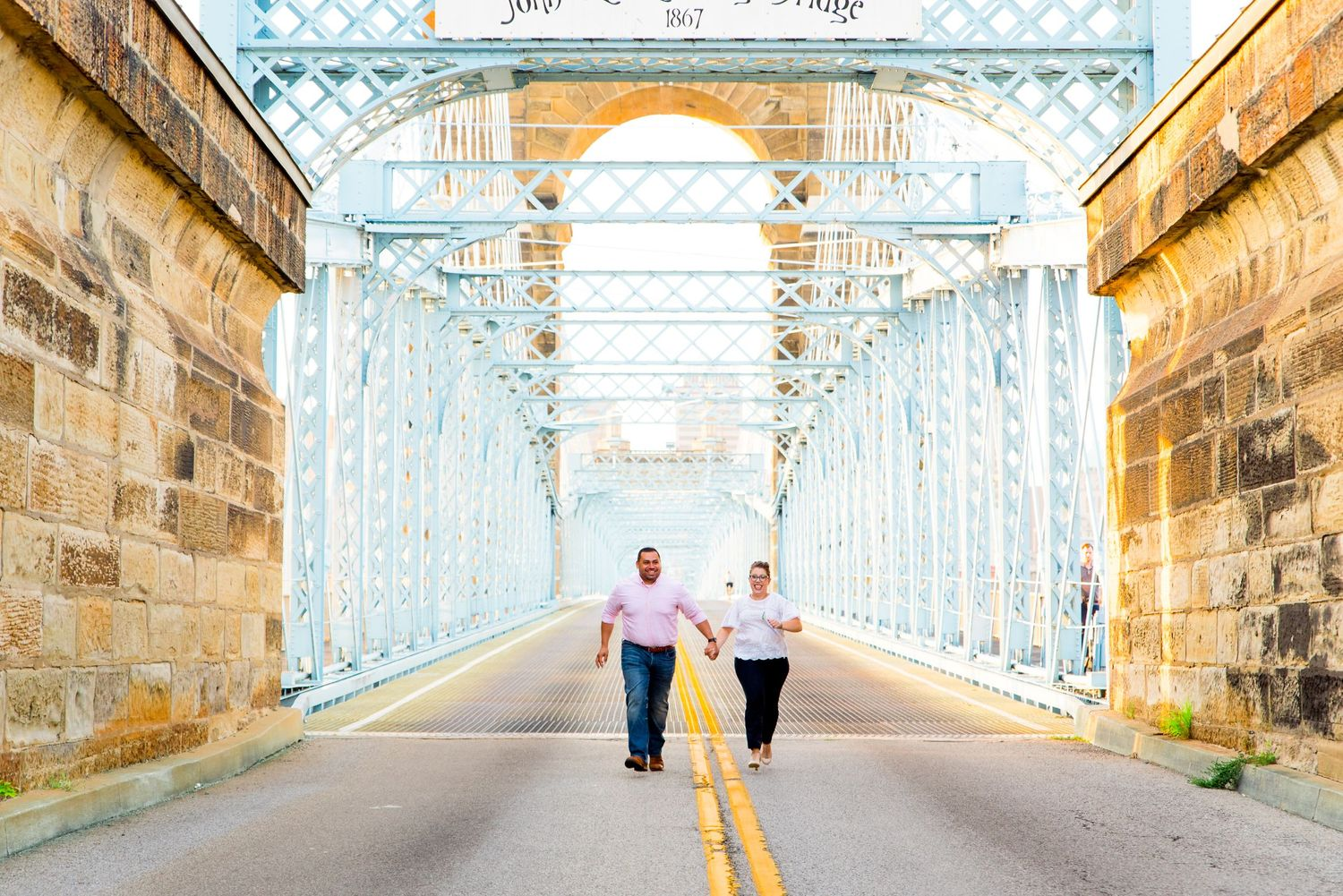 engaged couple holding hands and running through Roebling Bridge in downtown Cincinnati