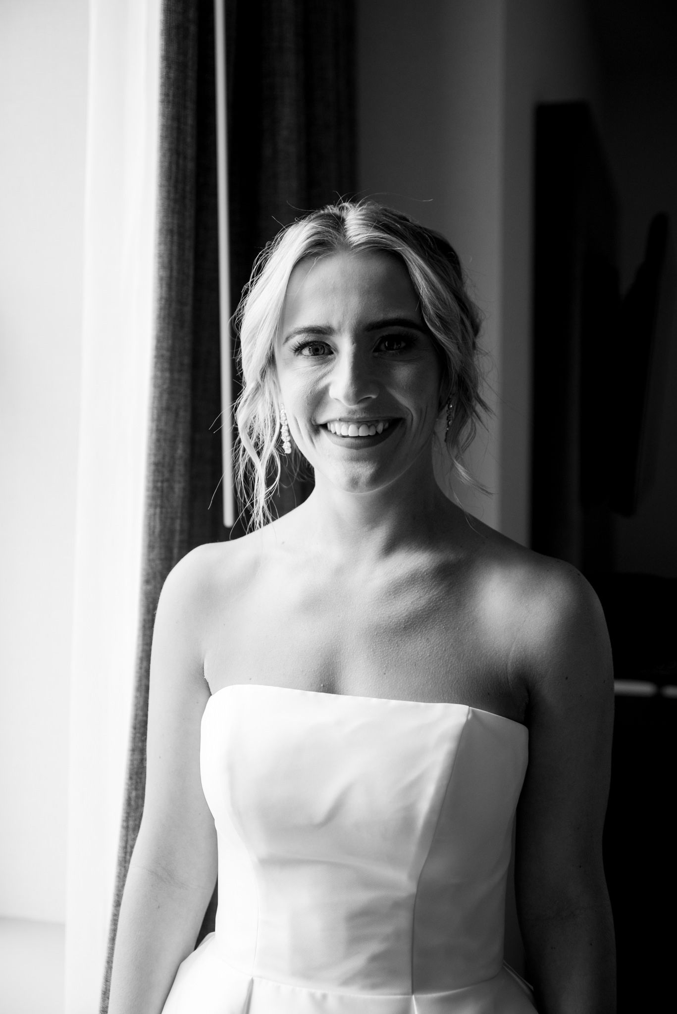 blonde bride with updo and strapless wedding dress smiling while getting ready