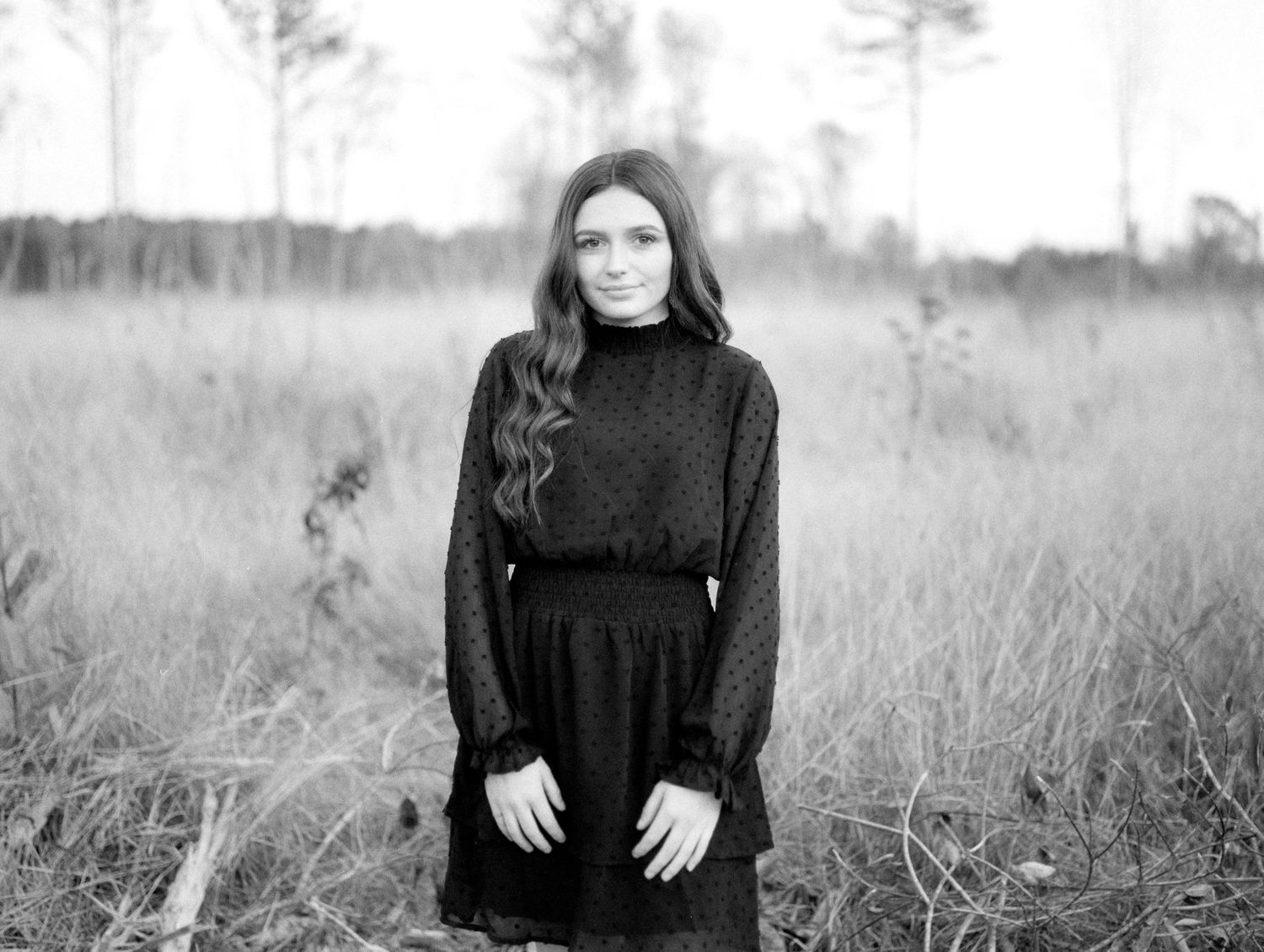 Black and white Louisiana senior portrait of female Franklinton High School student in an open field