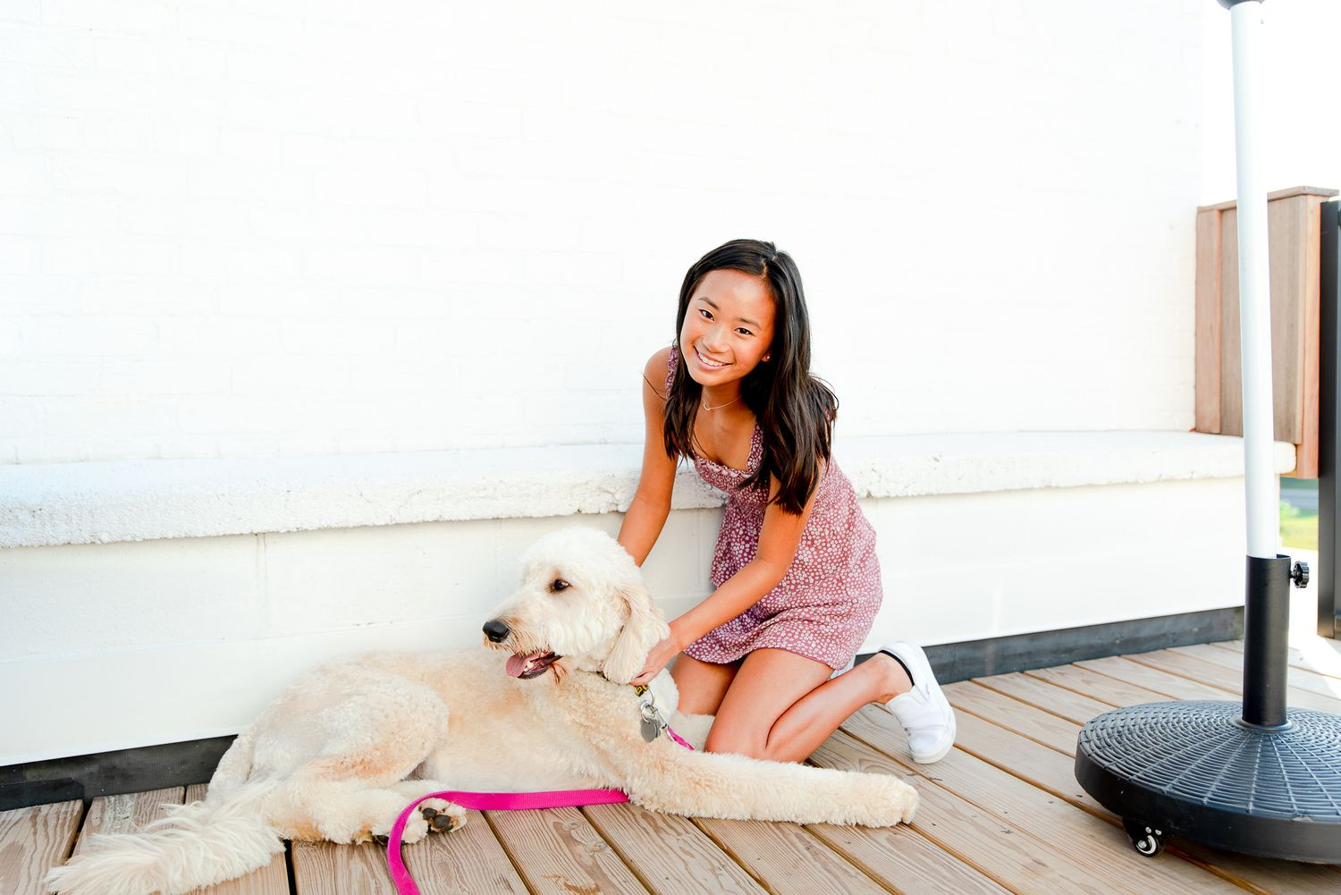 high school senior girl kneeling down to pet her dog in front of a white wall