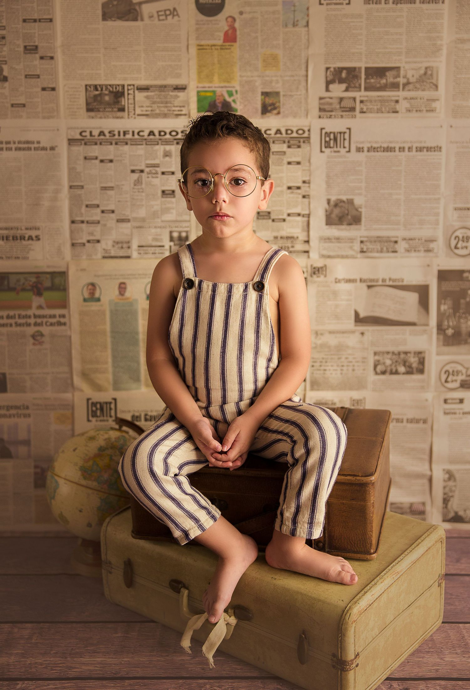 child sits on luggage newspaper backdrop