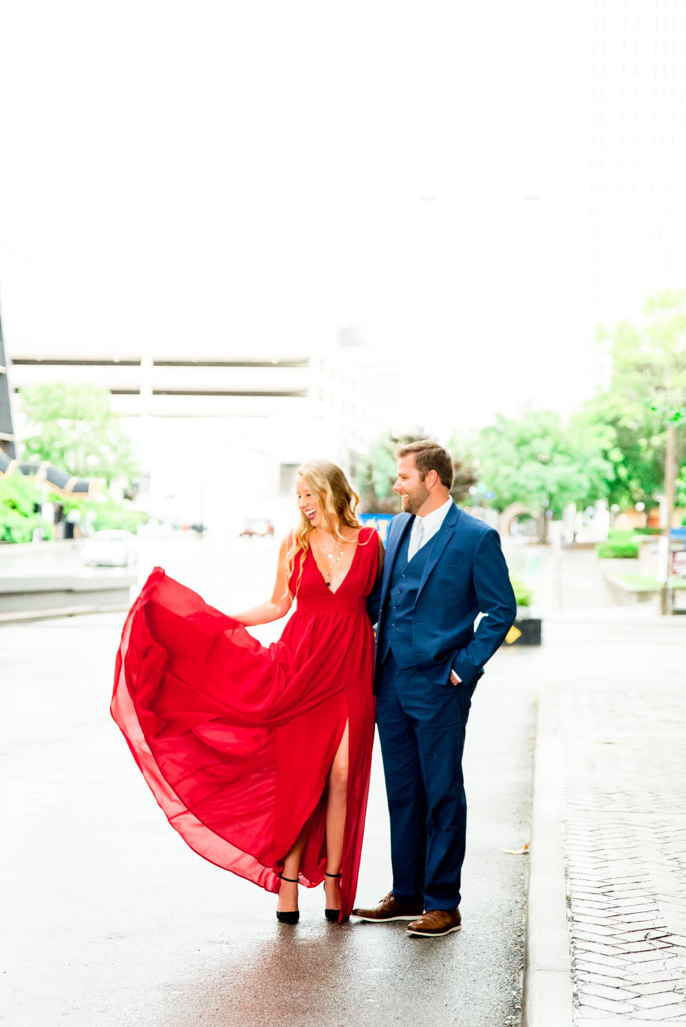 blonde woman in red dress holds hand leading fiance in navy suit outdoors