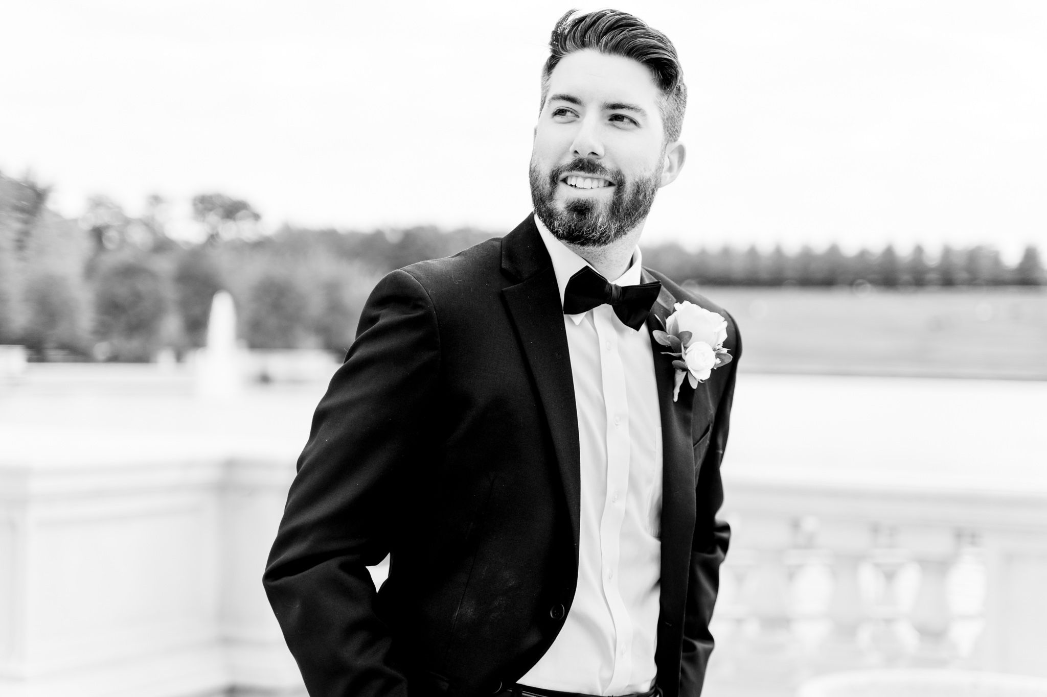 brunette groom with beard in black suit and bowtie smiles off to the side for St. Louis fall wedding