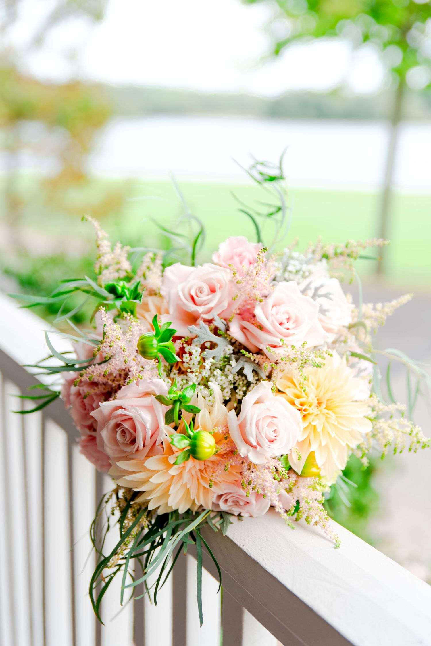 pastel spring wedding bouquet with pink roses and yellow dahlias, plus lamb's ear and pops of neon green