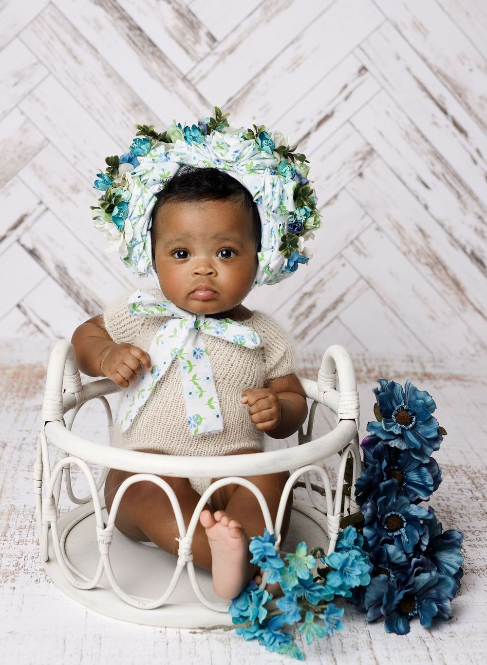 six month baby session sitting milestone baby in flower bonnet at austin baby studio austin newborn photography