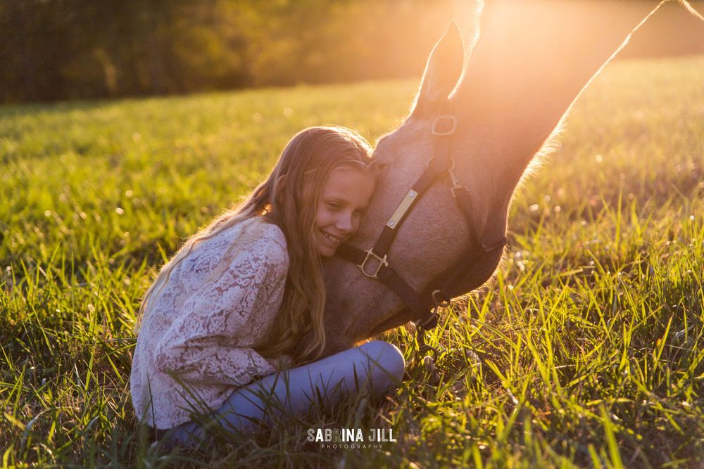 girl hugging her horse's head