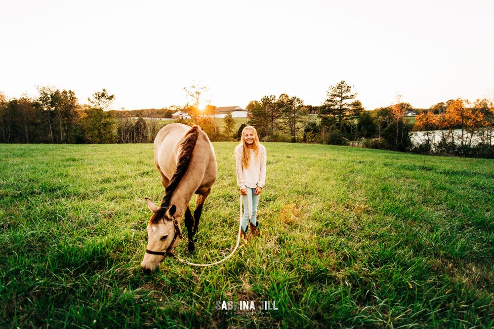 Girl standing next to her horse in a Waxhaw, NC field