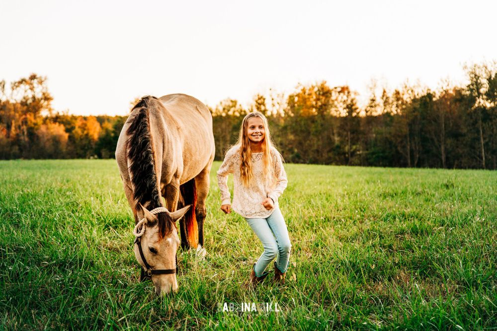 Girl dancing in field next to her horse