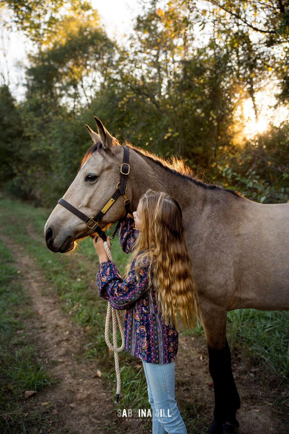 Girl holding onto her horse