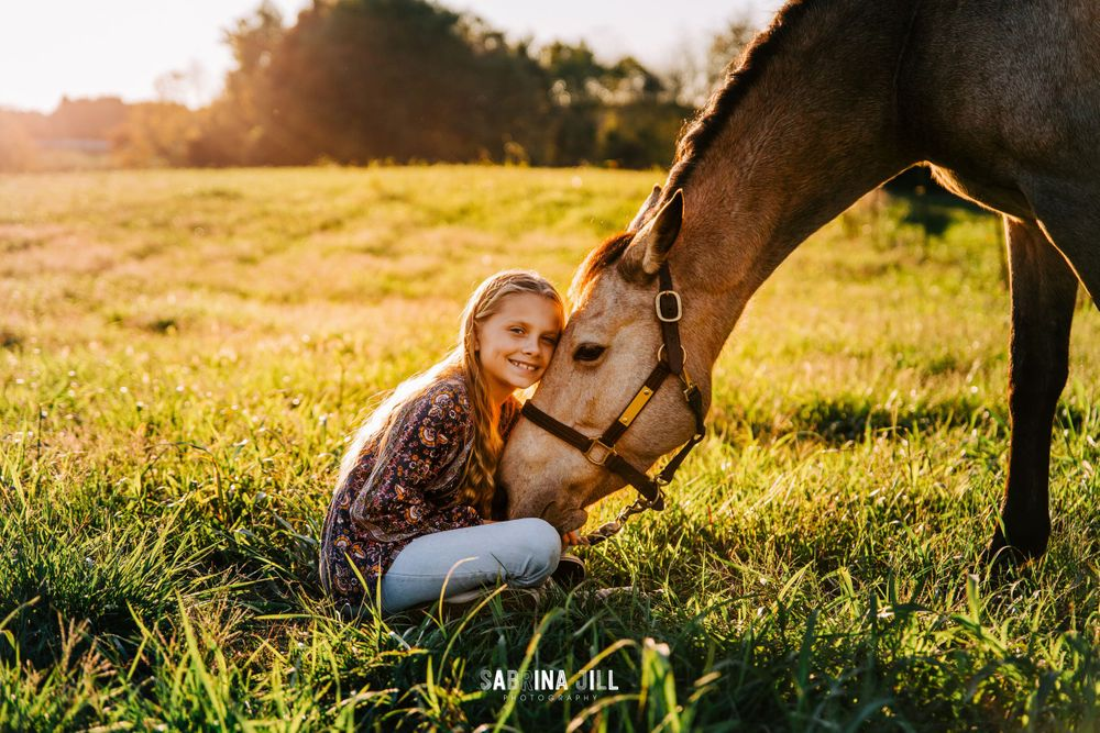 Girl sitting on ground hugging her horse's head
