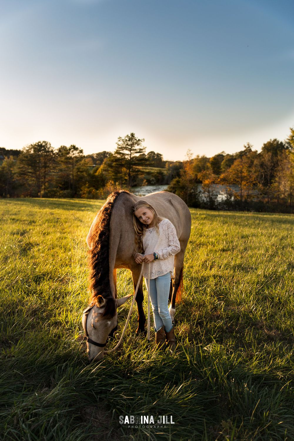 Girl leaning against her horse in field