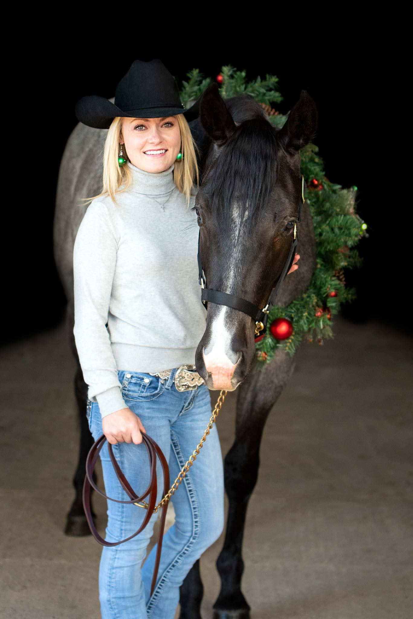 Woman posting with her horse in a christmas wreath