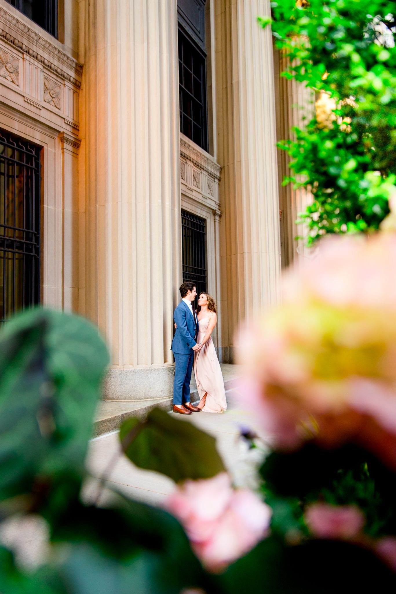 man and woman holding hands looking at each other by the pillars at Chicago Board of Trade for engagement pictures