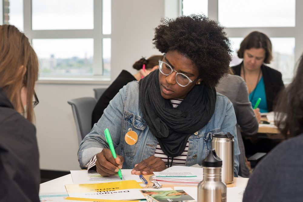 A black woman seated at a table with other working on a collaborative activity.