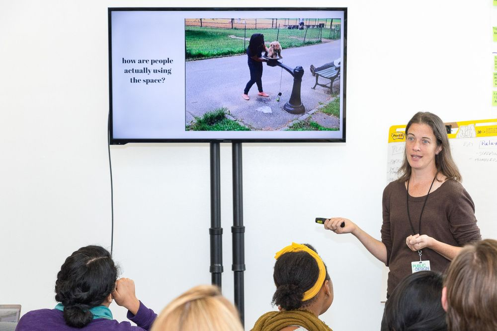 A white women presenting from a slideshow to a group of attendees during a conference breakout session.