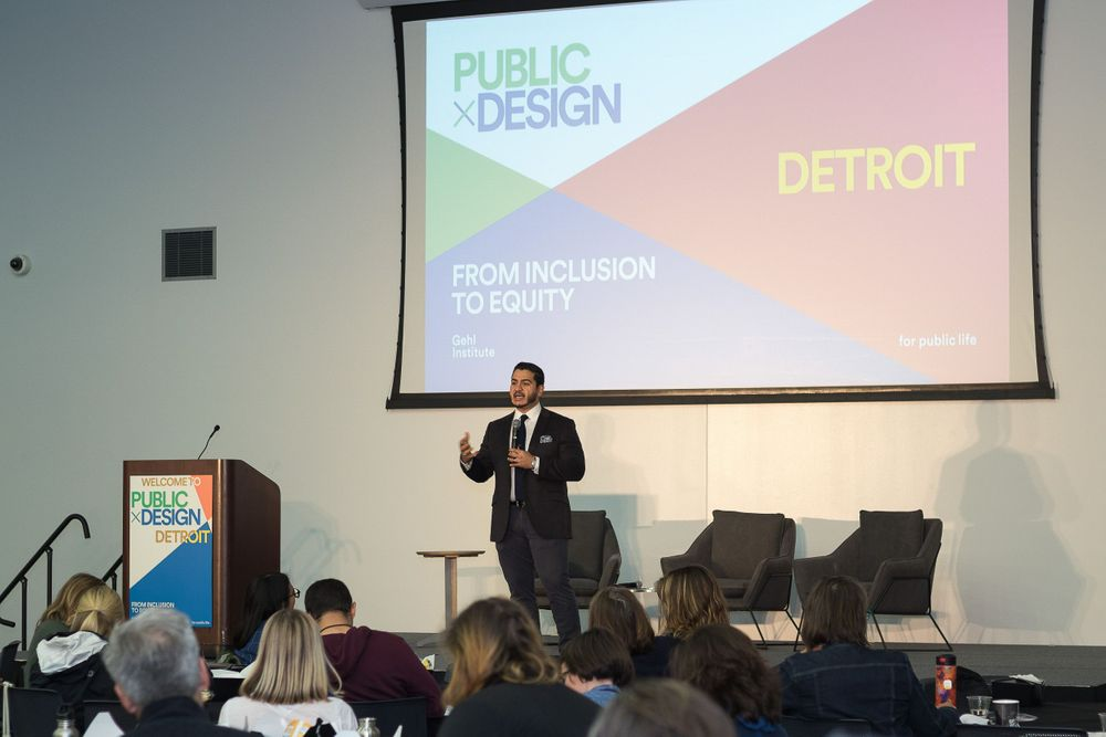 A gentleman giving a keynote presentation to a group of attendees at a public design conference.