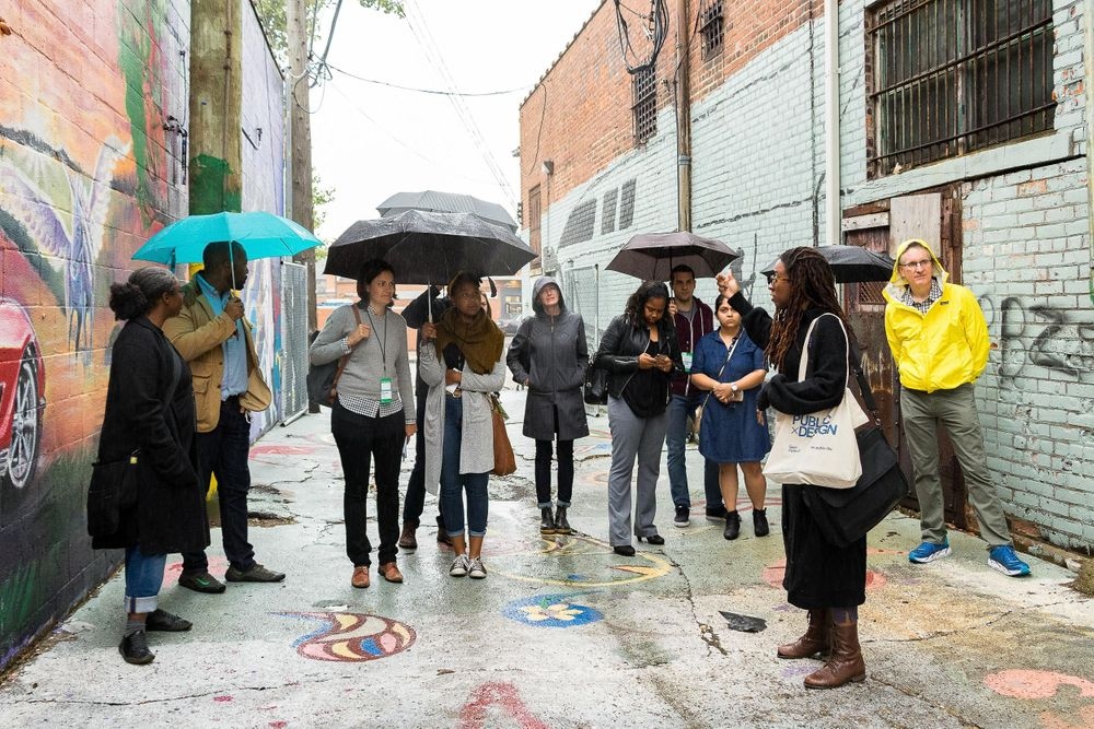 A group of people standing in the rain with umbrellas in an artist alley in Detroit.